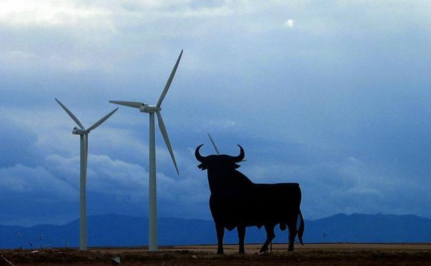 Un toro de Osborne junto a un parque eólico.