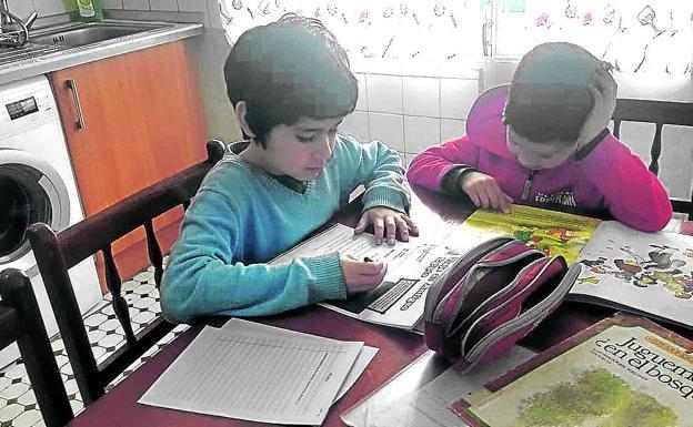 Evan y su hermano Diogo, de 6 y 9 años, realizan sus tareas en la mesa de la cocina.